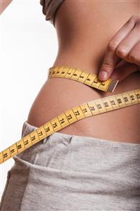 Photo: Woman measuring her waist